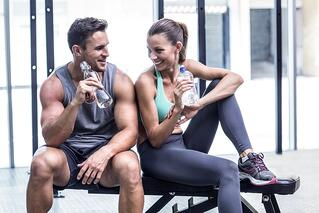 Muscular couple discussing on the bench and holding water bottle.jpeg