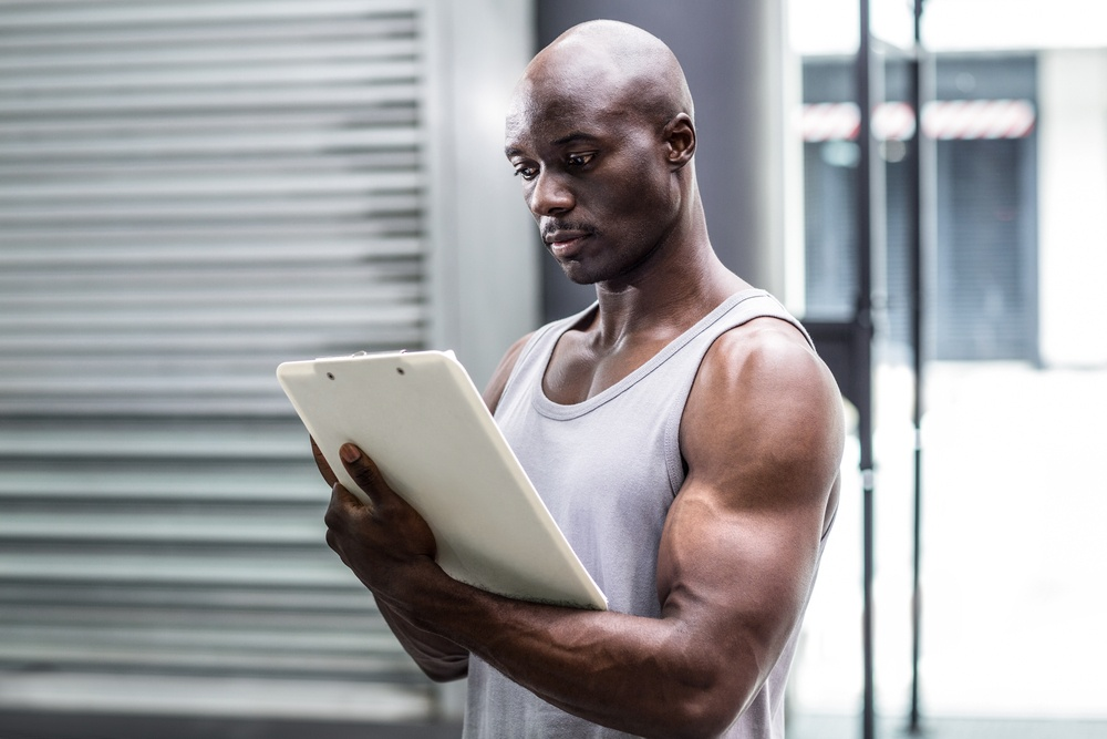 Side view of a muscular trainer writing on clipboard.jpeg